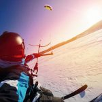 Selfie_action_camera_Skier_with_kite_rides_on_frozen_lake_on_free_ride._Russia._Snowkite_sunset.
