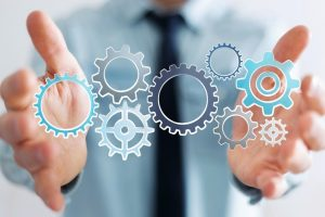 Businessman_on_blurred_background_holding_hand-drawn_gears_icons