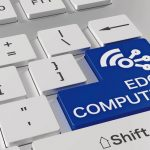 White_computer_keyboard_with_a_blue_enter_key_showing_edge_computing_and_a_wireless_network_icon_3D_illustration