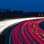 Viele_Autos_fahren_bei_Nacht_auf_einer_Autobahn_und_erzeugen_Lichtspuren.
